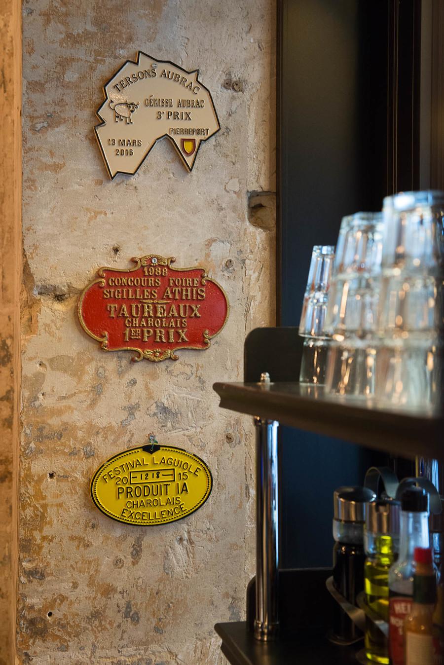 Intérieur du Café Jussieu de Paris avec son panneau décor, ses suspensions croisillon et ses assises en cuir.