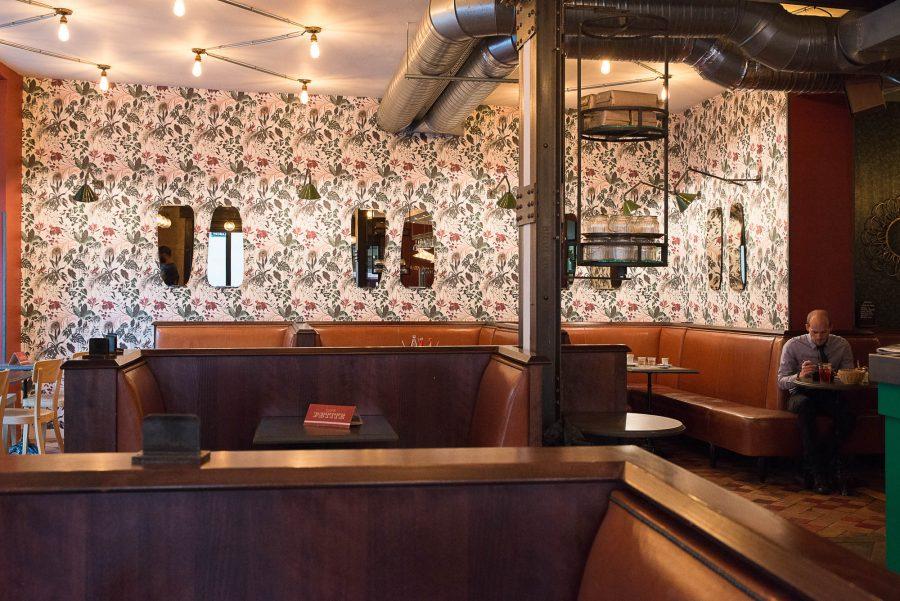 Intérieur du Café Petite à Paris avec sa banquette en cuir naturelle et papier peint fleuris décoration par le Studio Emma Roux