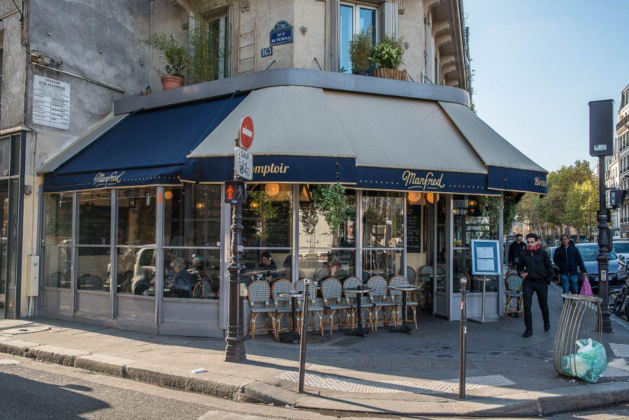 Extérieur de la brasserie Le Manfred à Paris, store bleu marine et mobilier extérieur signé Maison Gatti. Décoration par le Studio Emma Roux