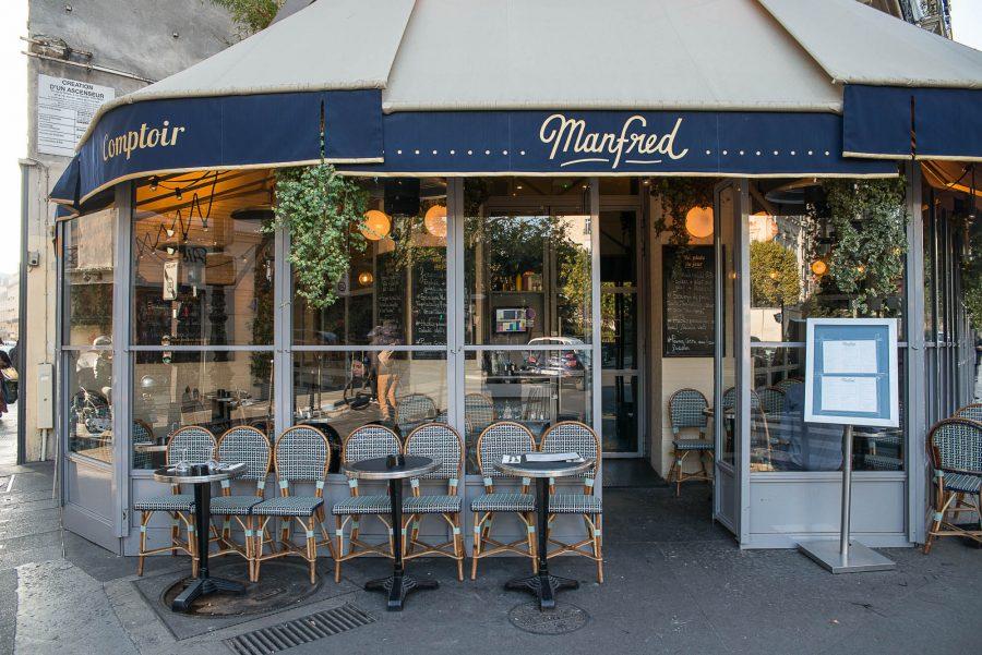 Extérieur du restaurant Le Manfred à Paris, store bleu marine et mobilier extérieur signé Maison Gatti. Décoration par le Studio Emma Roux