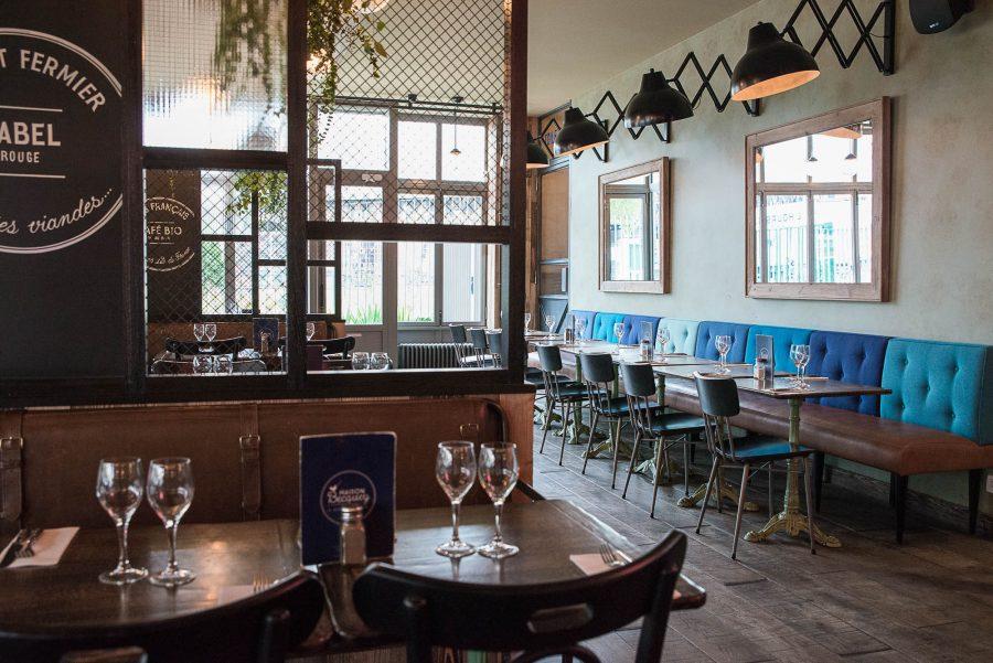 Intérieur de la rôtisserie Maison Becquey de Paris, banquette avec assises en cuir, dossiers nuancés de bleu et luminaires croisillons. Décoration par le Studio Emma Roux