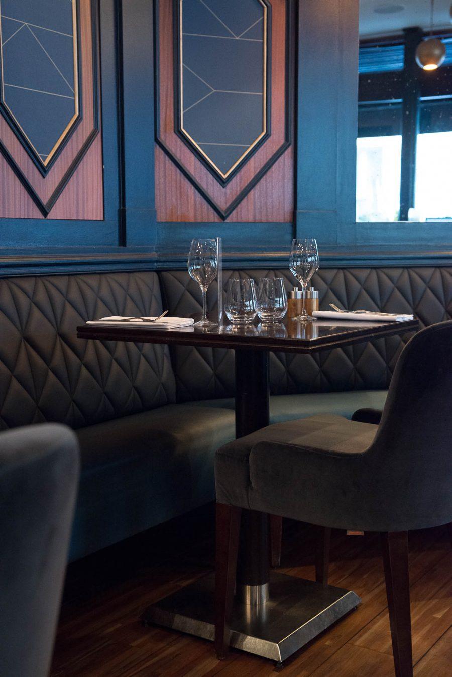 Intérieur du restaurant Le Marloe de Paris avec banquette en cuir matelassée et panneaux décoratifs de bois au motif hexagonal