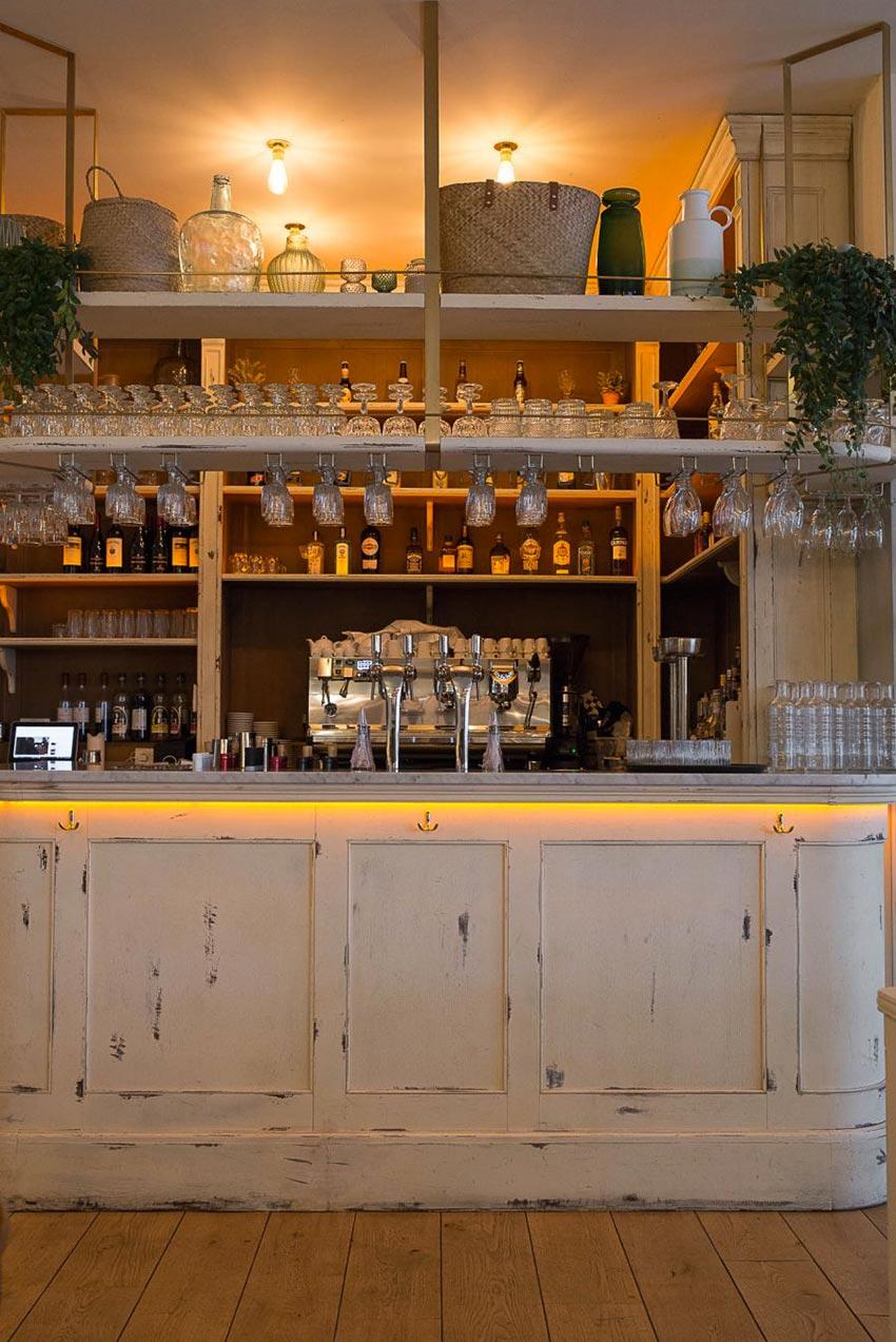 Intérieur du restaurant Simonetta de Paris. Comptoir en bois vieilli et parquet au sol. Décoration par le Studio Emma Roux