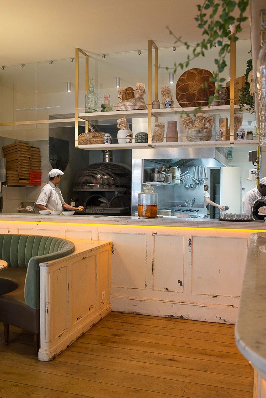 Intérieur de la pizzeria Simonetta de Paris. Comptoir en bois blanc vieilli, cuisine apparente. Décoration par le Studio Emma Roux