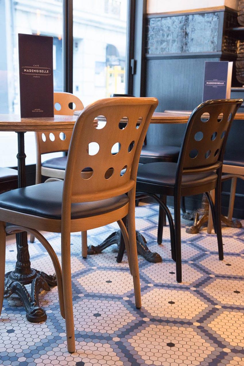 Intérieur du Café Mademoiselle de Paris. Chaise en bois et sol en mosaique Whickelmans.