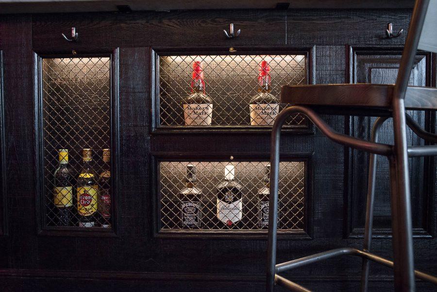 Intérieur de la rôtisserie Maison Becquey, détails du comptoir grillagés et chaise haute en bois. Décoration par le Studio Emma Roux