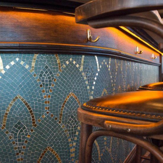 Comptoir en bois et mosaique de la brasserie Le Manfred à Paris avec ses chaises en bois et assises en cuir. Décoration par le Studio Emma Roux