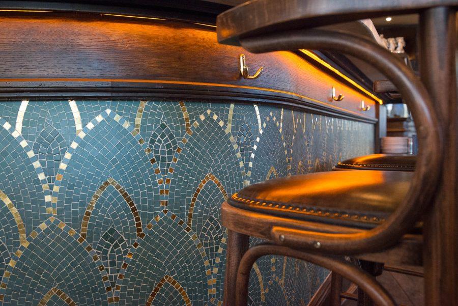 Comptoir en bois et mosaique du restaurant Le Manfred à Paris avec ses chaises en bois et assises en cuir. Décoration par le Studio Emma Roux