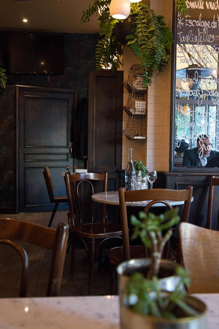 Intérieur du restaurant Le Manfred à Paris, plantes en suspension et chaises en bois. Décoration par le Studio Emma Roux