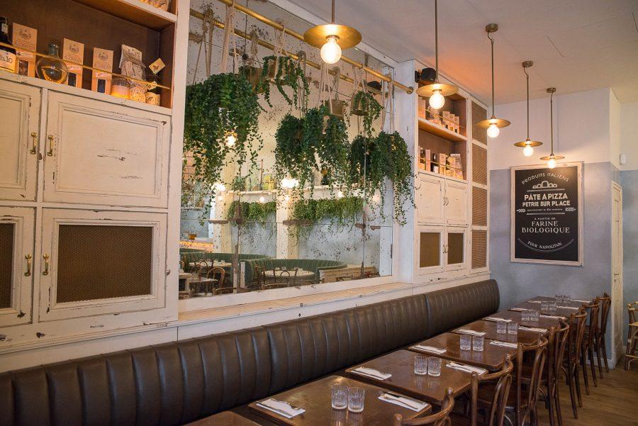 Intérieur du restaurant Simonetta, luminaires dorés et plantes suspendus. Assises des chaises et de la banquette en cuir. Décoration par le Studio Emma Roux.