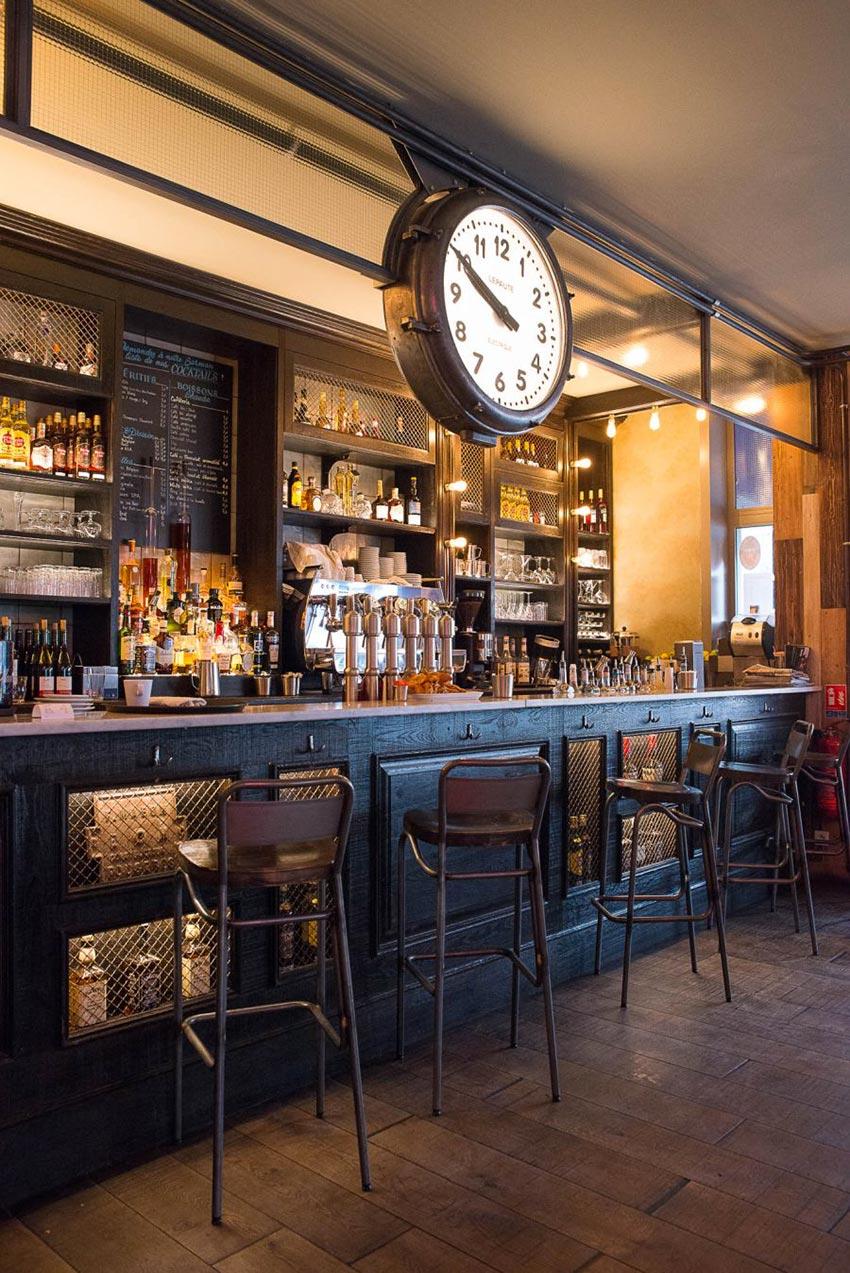 Intérieur de la rôtisserie Maison Becquey, on retrouve un comptoir, chaises et cadran d'époque. La décoration a été faite par le Studio Emma Roux