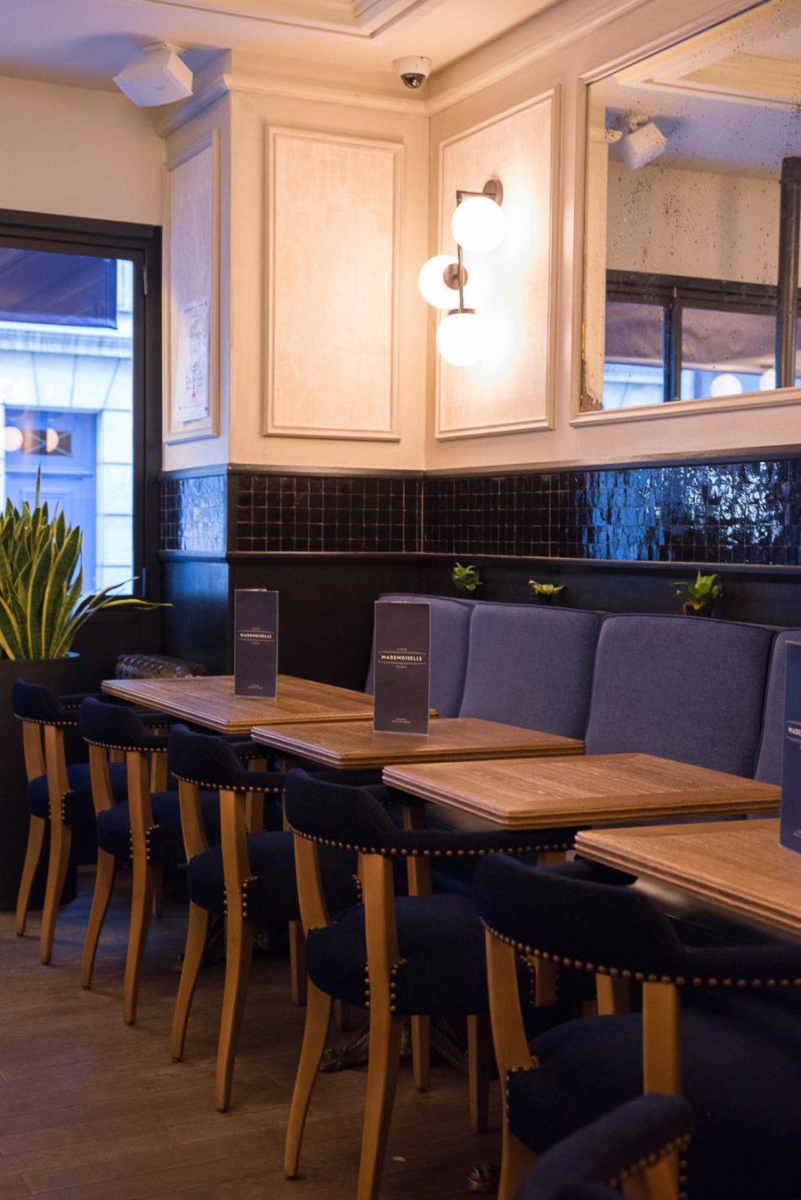 Intérieur du Café Mademoiselle de Paris avec une dominante de bleu sur les chaises, la banquette et la frise en zellige.
