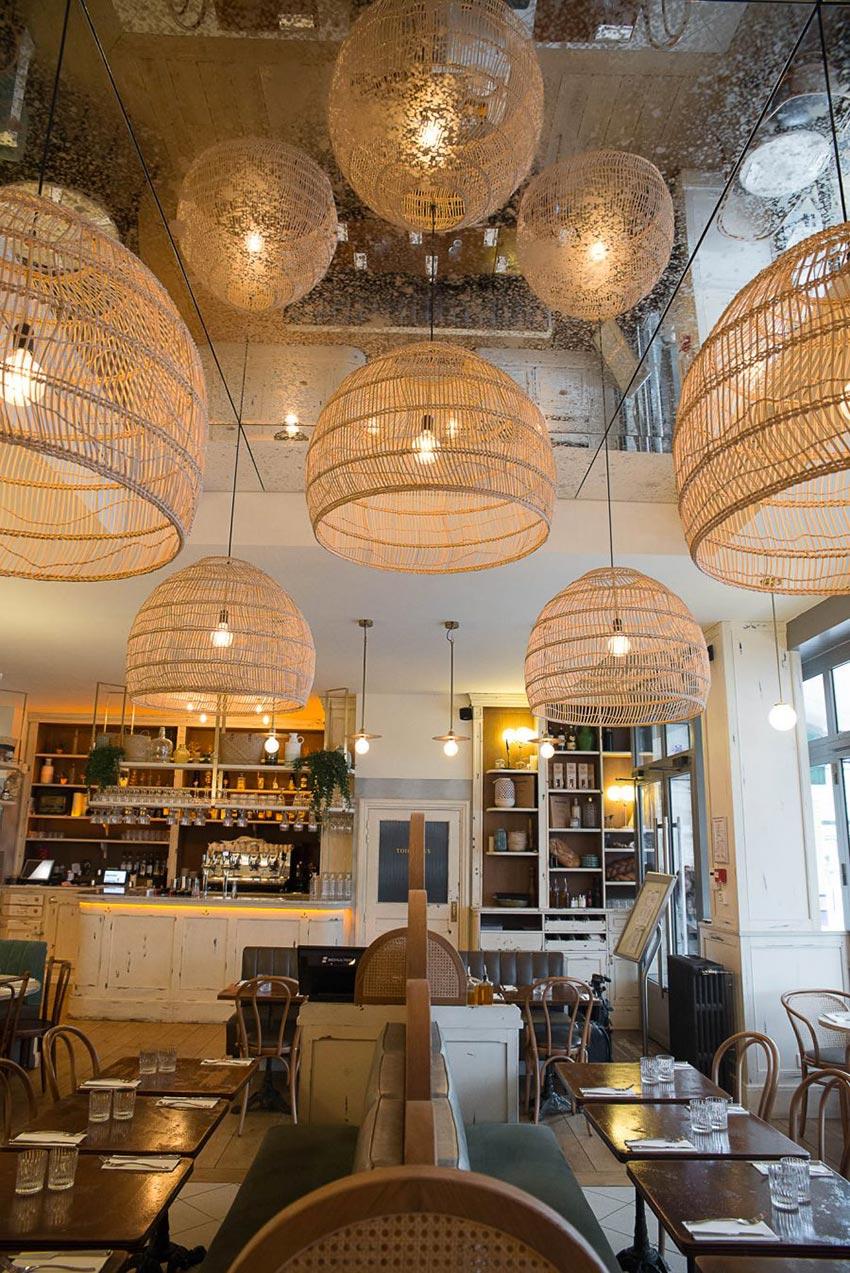 Intérieur du restant Simonetta de Paris avec un miroir étendu au plafond. Luminaires naturels en suspension. On aperçoit au fond le comptoir en bois blanc vieilli. Décoration par le Studio Emma Roux