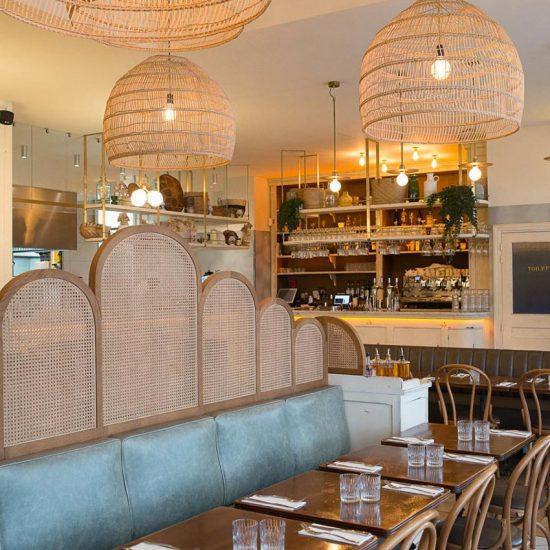 Intérieur du restant Simonetta de Paris avec des luminaires naturels en suspension. On aperçoit au fond le comptoir en bois blanc vieilli. Décoration par le Studio Emma Roux