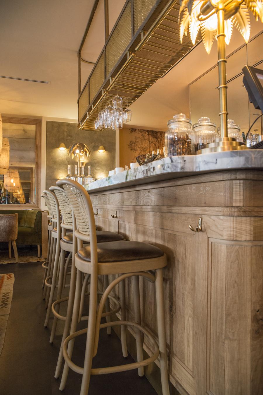 Restaurant Le Murillo de Paris - Décoration Emma Roux. Chaises en cannage, marbre, bois brut, luminaire en laiton.