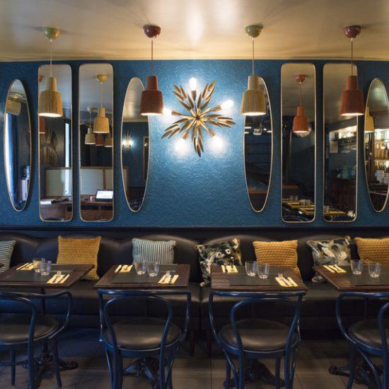 Restaurant Chez Plumeau à Montmartre - Décoration Studio Emma Roux. Jeux de miroir, appliques vintage en laiton, coussins à motifs, suspensions à frange.