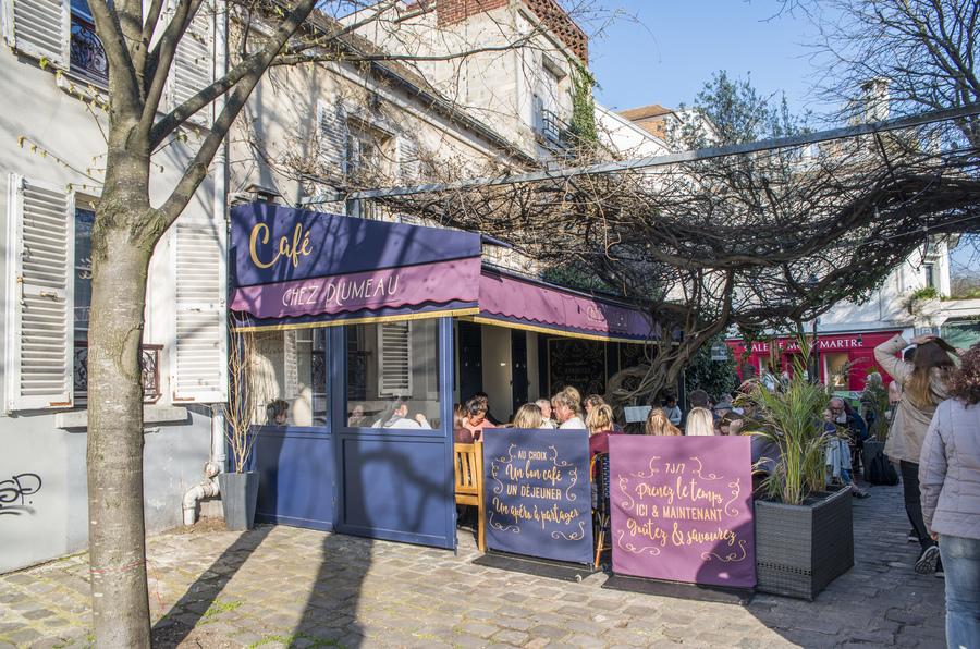 Restaurant Chez Plumeau à Montmartre - Décoration Studio Emma Roux. Panneaux extérieur, signalétique, chaises en cannage et store coloré.