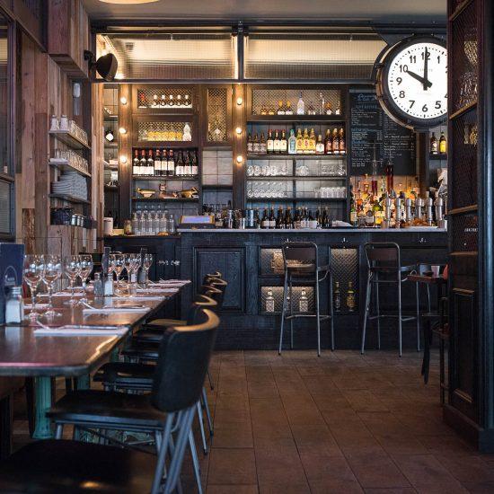 Intérieur de la rôtisserie Maison Becquey, avec son comptoir en bois, sa banquette de cuir, son cadran suspendu et son parquet. Décoration par le Studio Emma Roux