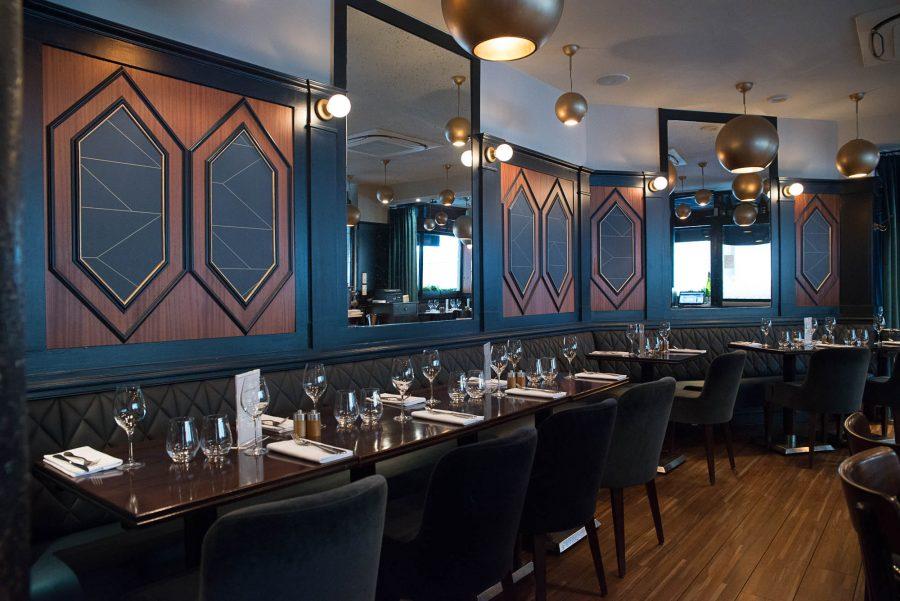 Intérieur du restaurant Le Marloe de Paris avec banquette en cuir matelassée et panneaux décoratifs de bois au motif hexagonal.