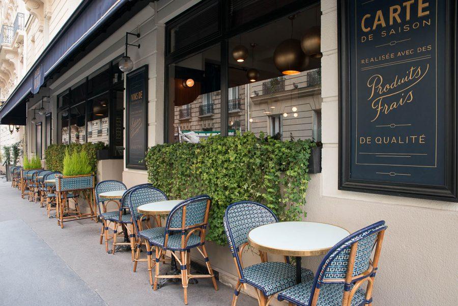 Terrasse extérieur du restaurant Le Marloe de Paris. Chaises en cannage par Maison Gatti. Store et panneaux décor bleu marine.