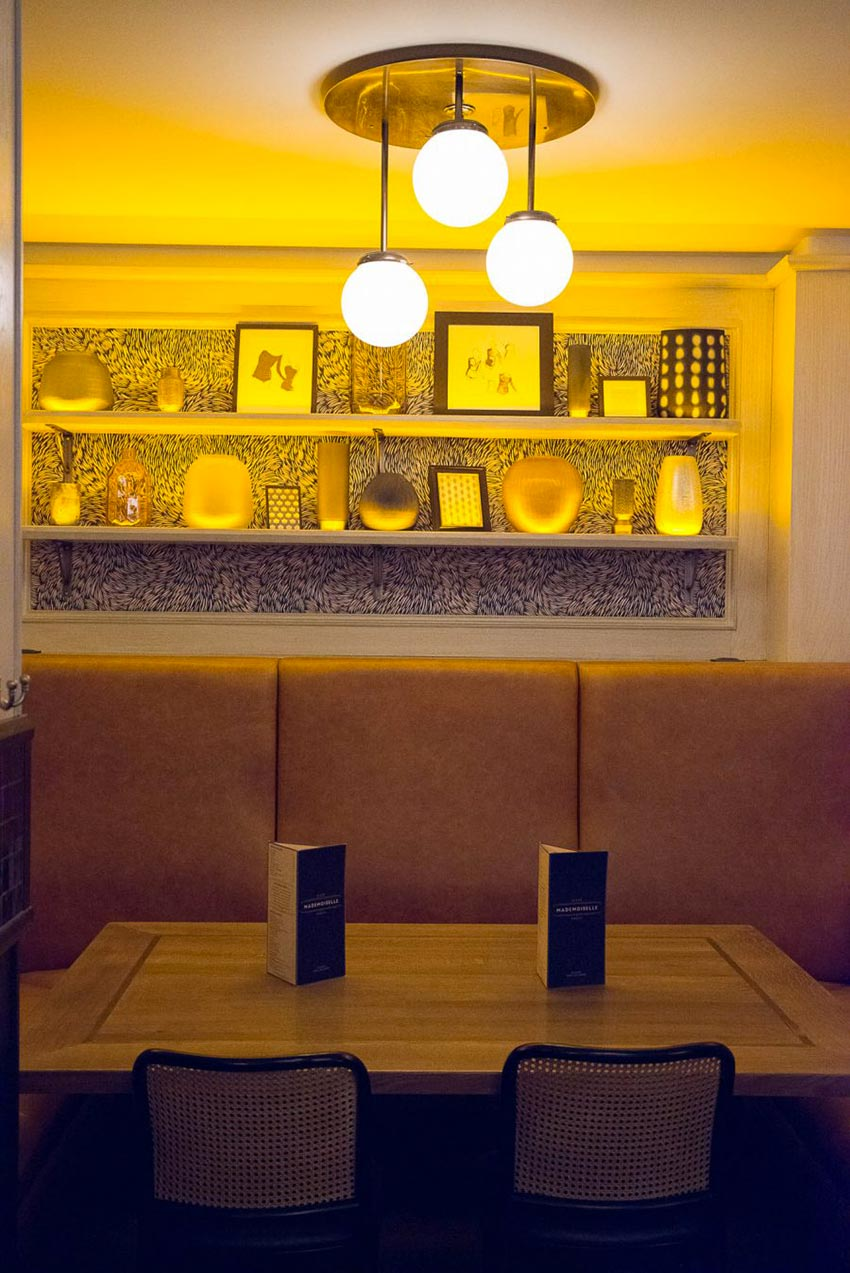 Banquette au dossier haut en cuir naturel et table d'hôtes du Café Mademoiselle de Paris avec son étagère et papier peint Petite Friture.