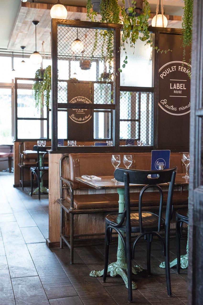 Intérieur de la rôtisserie Maison Becquey, banquette en cuir, parquet et plantes en suspension. Décoration par le Studio Emma Roux