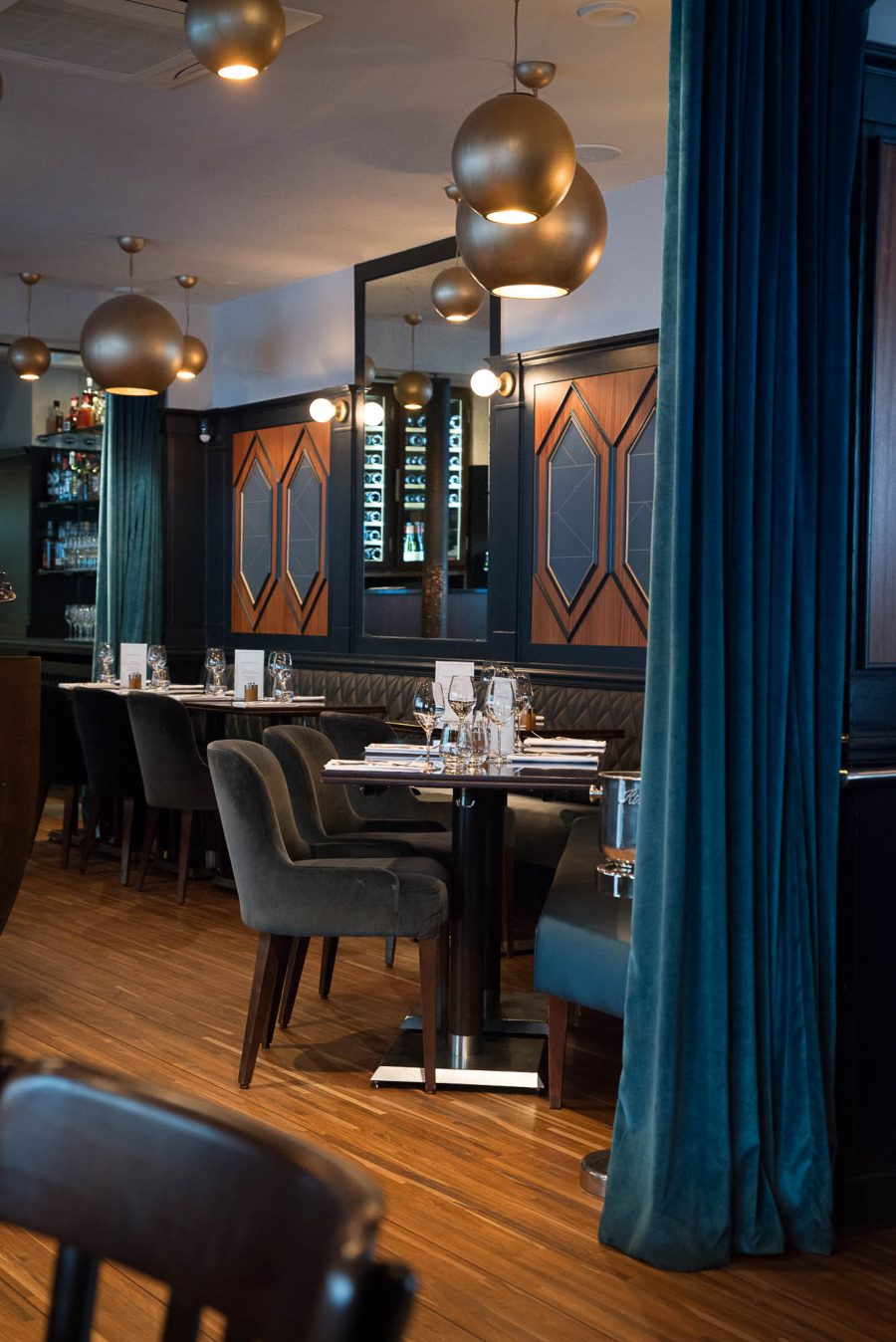 Intérieur du restaurant Le Marloe de Paris avec banquette en cuir matelassé, parquet et panneaux décoratifs de bois au motif hexagonal