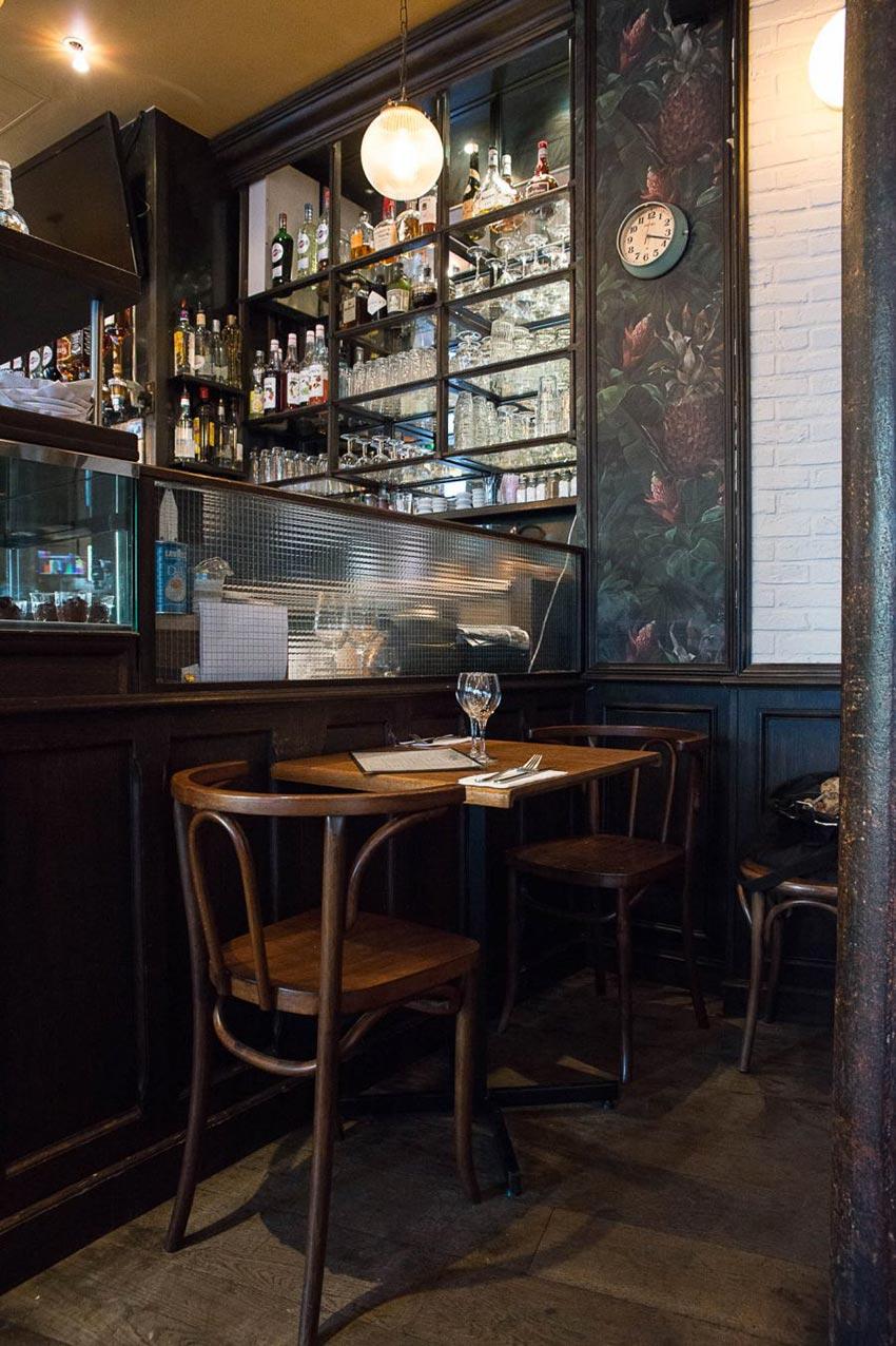 Intérieur de la brasserie Le Manfred à Paris, mobilier en bois et tapisserie floral. Décoration par le Studio Emma Roux