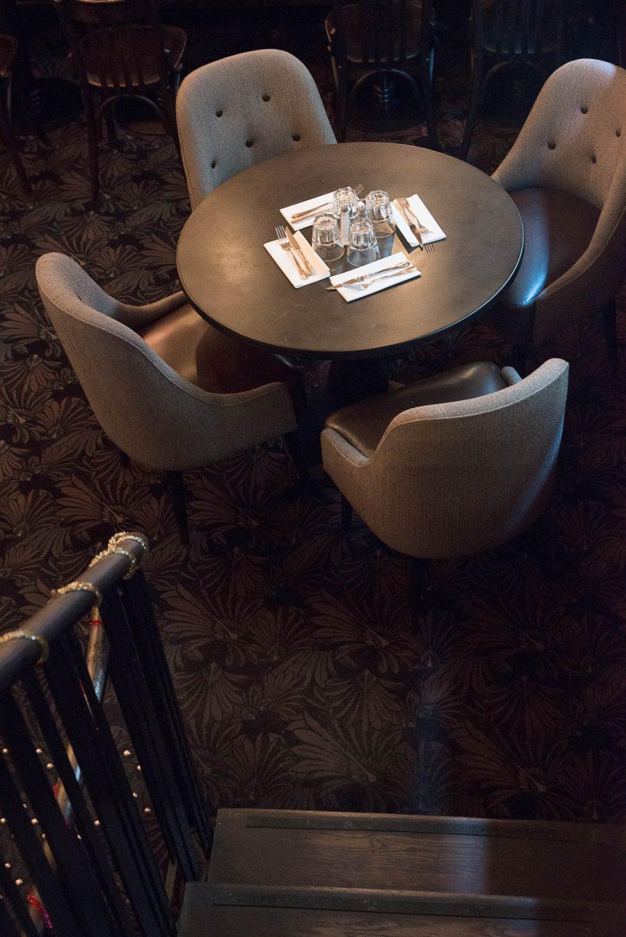Intérieur du restaurant Le Morny de Paris, moquette au sol et fauteuils avec assises en cuir. Décoration par le Studio Emma Roux