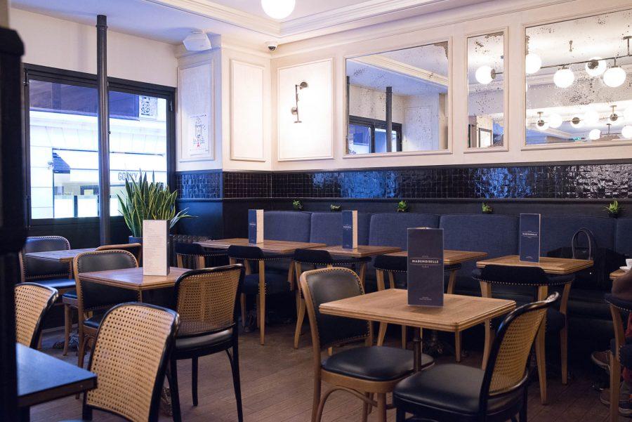 Salle en intérieur du Café Mademoiselle de Paris avec une dominante de couleur bleu. Parquet, frise en zellige et assortiment d'assises coordonnées.