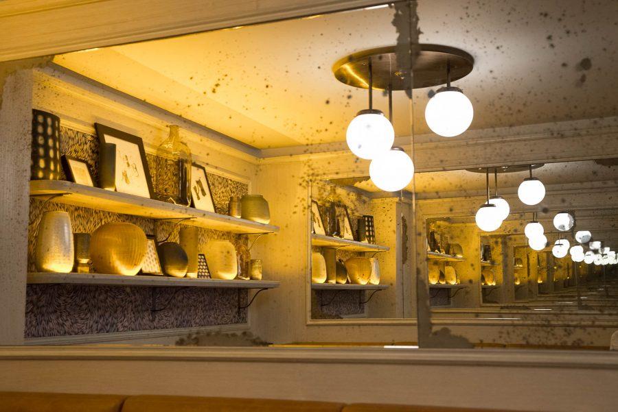 Miroir du Café Mademoiselle de Paris avec ses luminaires suspendus et ses étagères.