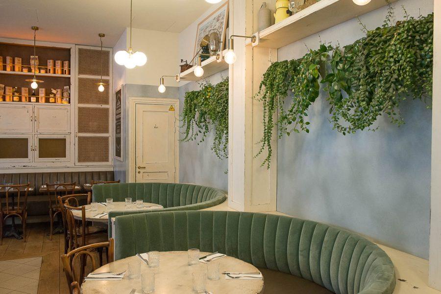 Intérieur du restaurant Simonetta de Paris. Banquette avec dossiers en velour et assises en cuir. Plantes et luminaires en suspension. Décoration par le Studio Emma Roux.