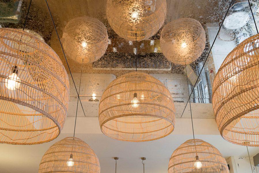 Intérieur du restant Simonetta de Paris avec un miroir étendu au plafond. Luminaires naturels en suspension. Décoration par le Studio Emma Roux