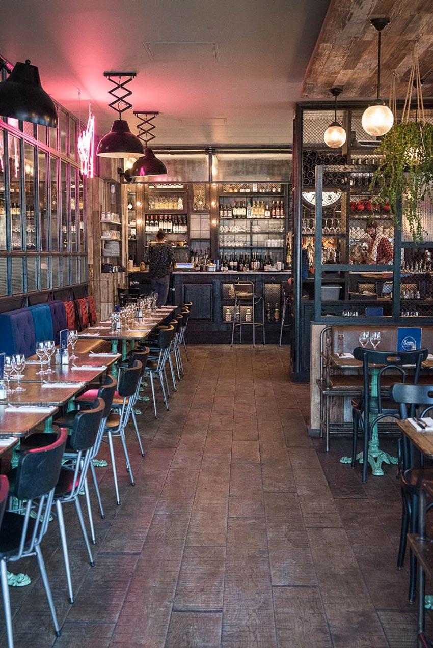 Intérieur de la rôtisserie Maison Becquey de Paris, banquette avec assises en cuir, dossiers nuancés de bleu, néon rose, parquet et luminaires croisillons. Décoration par le Studio Emma Roux