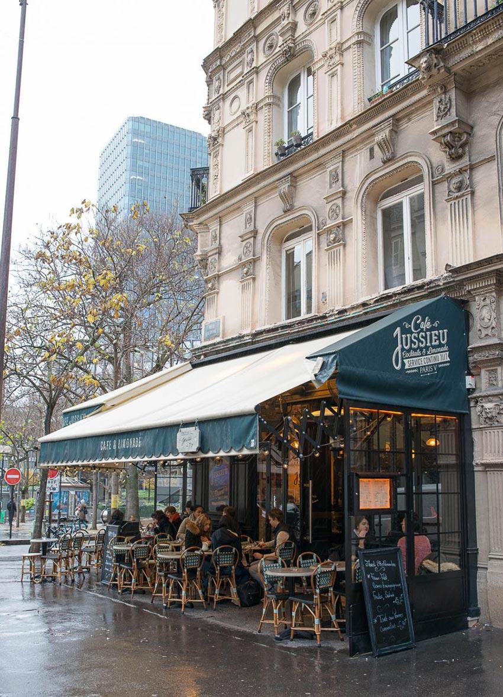 Terrasse extérieure du Café Jussieu de Paris où on aperçoit son store et ses chaises en cannage