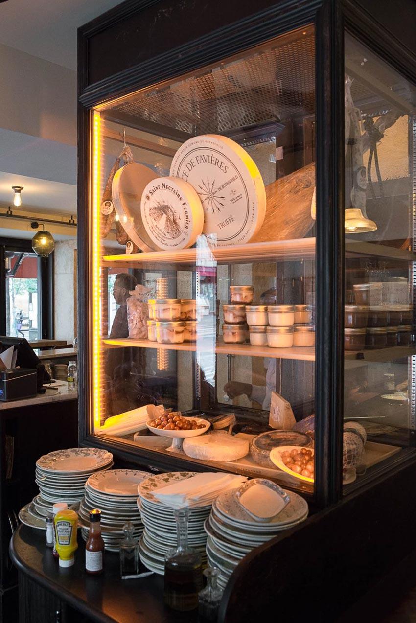 Vitrine frigorifique du Café Bolivar à Paris où l'on aperçoit des produits français: fromages et charcuteries. Décoration par le Studio Emma Roux.