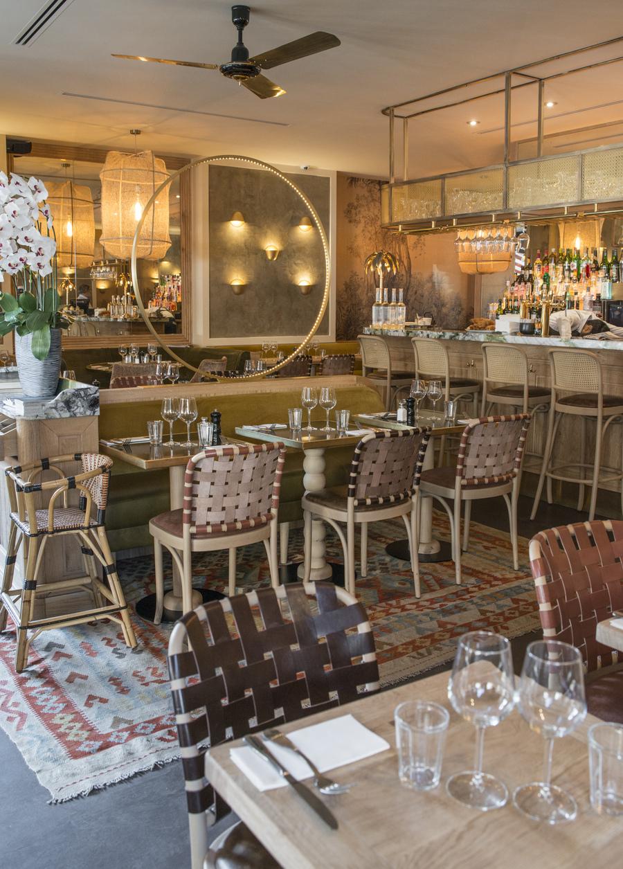 Restaurant Le Murillo de Paris - Décoration Emma Roux. Chaises tressées de cuir, banquette en velour, tapis kilim, luminaire en laiton.