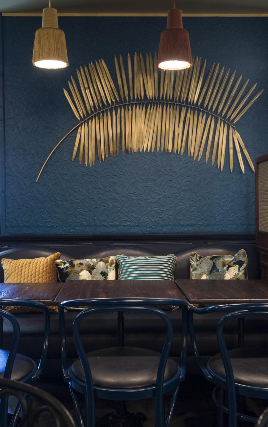 Restaurant Chez Plumeau à Montmartre - Décoration Studio Emma Roux. Applique décorative en laiton, coussins à motifs.